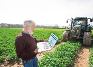 Farmer with laptop in canola field fot. Bayer